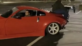 Man tries to hold onto car while performing drift