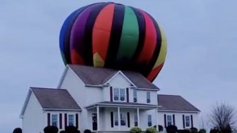 Hot air balloon lands on house
