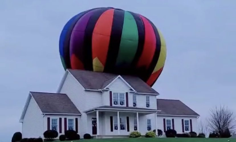 Hot air balloon lands on house